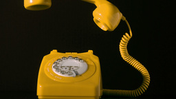 Receiver falling on yellow dial phone on black bac Footage