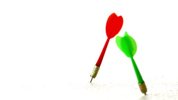 Red and green darts piercing white surface Stock Video Footage