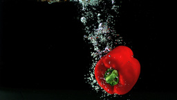 Red pepper falling in water and floating Stock Video Footage