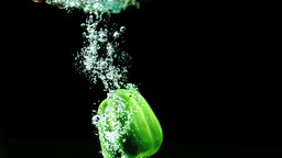 Green pepper falling in water and floating Footage