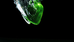 Green pepper falling in water and floating Stock Video Footage