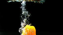 Yellow pepper falling in water and floating Stock Video Footage