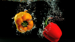 Two peppers falling in water and floating Footage