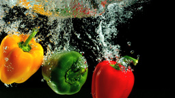 Three peppers falling into water and floating Footage