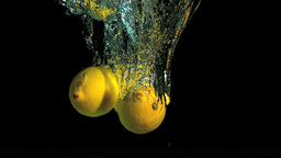 Two lemons dropping into water Stock Video Footage