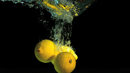 Two lemons dropping into water Footage