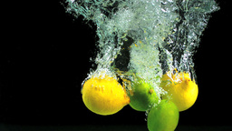 Lemons and limes dropping into water Stock Video Footage