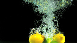 Lemons and limes dropping into water Footage