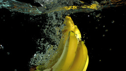 Bunch of bananas falling in water Footage