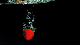 Strawberry falling into water Footage