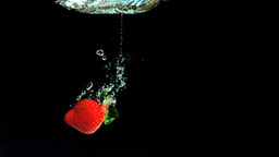 Strawberry falling into water and floating Stock Video Footage