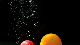 Apple and orange falling in water Stock Video Footage