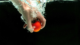 Hand grabbing tomato from water Live Action