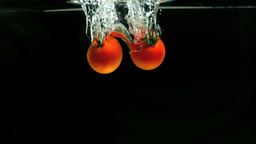 Two tomatoes falling in water Stock Video Footage