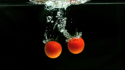 Two tomatoes falling in water Footage