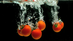 Tomatoes falling into water Stock Video Footage