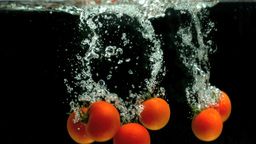 Tomatoes falling into water Footage