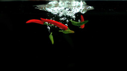 Red and green chilies falling into water Footage
