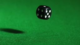 Black dice falling on green table close up Footage