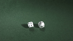 White dice rolling on green table Footage