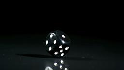 Black dice falling on black background Footage