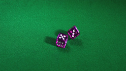 Purple dice rolling on green table Footage