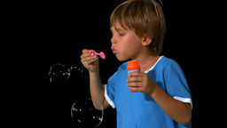Boy blowing bubbles on black background Stock Video Footage