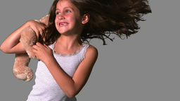 Little girl twirling and catching teddy on grey background Footage