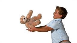 Little boy jumping and catching teddy on white bac Stock Video Footage