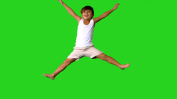 Happy little boy jumping on green screen Footage