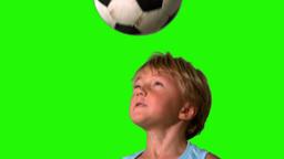 Little boy heading football on green screen Footage