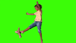 Boy jumping to kick teddy bear on green screen Footage