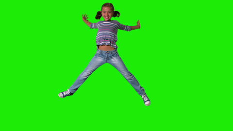 Smiling girl jumping up and down on green screen Stock Video Footage