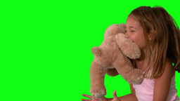Cute little girl catching teddy bear on green scre Footage