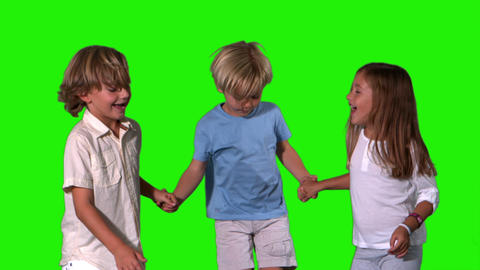 Siblings holding hands and jumping on green screen Stock Video Footage
