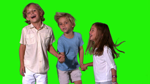 Siblings holding hands and jumping on green screen Footage