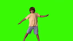 Little boy jumping with limbs outstretched on gree Footage