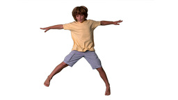 Little boy jumping with limbs outstretched on whit Stock Video Footage