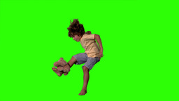Little boy jumping up and kicking teddy bear on green screen Stock Video Footage