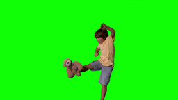 Little boy jumping up and kicking teddy on green screen Footage