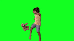 Little boy jumping up and kicking teddy on a green Stock Video Footage
