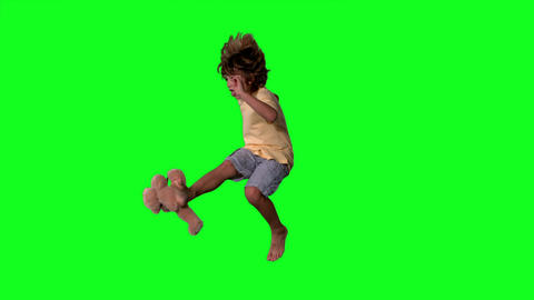 Little boy jumping up and kicking teddy on a green screen Footage