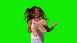 Little girl jumping up and turning with teddy on green screen Footage