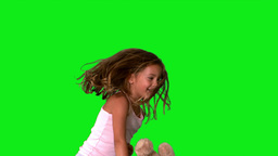 Little girl jumping up and down and turning with teddy on green screen Footage