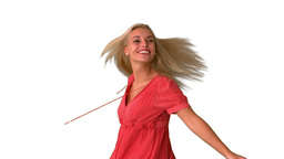 Attractive blonde twirling on white background Footage