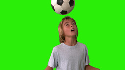 Young boy heading and kicking a football on green  Footage