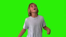 Young boy heading and kicking a football on green Stock Video Footage