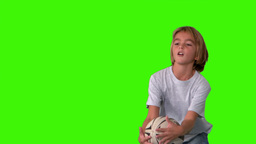 Boy catching rugby ball on green screen Footage