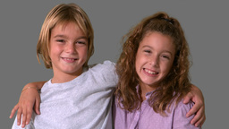 Siblings smiling on grey background Stock Video Footage