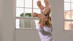 Girl in pajamas jumping and swinging teddy bear in Footage